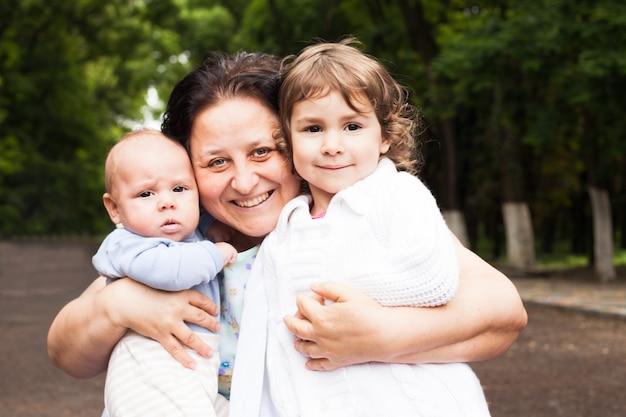 Grootmoeder met haar kleinkinderen in een park. familieportretten