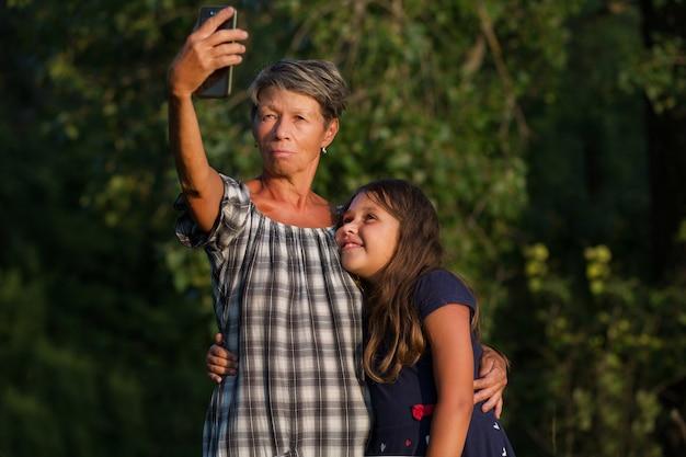 Grootmoeder met kleindochter die selfi 's avonds buiten maakt