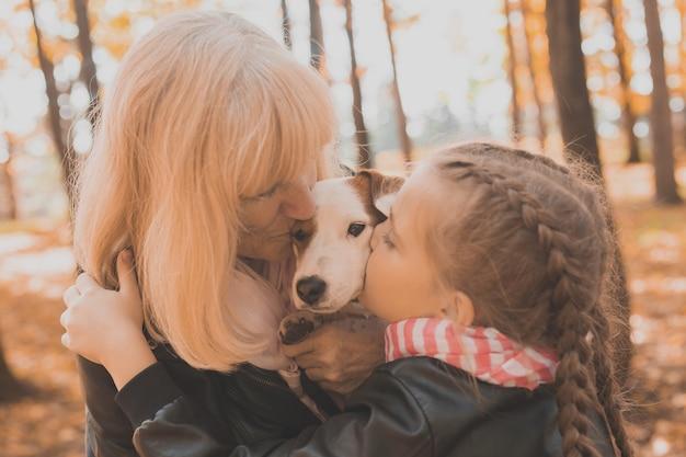 Grootmoeder met kleindochter in het herfstparkmeisje dat grootmoeder en haar jack russell-terriër knuffelt