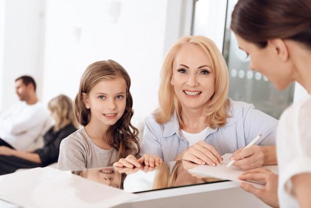 Grootmoeder met kleindochter vult documenten in.