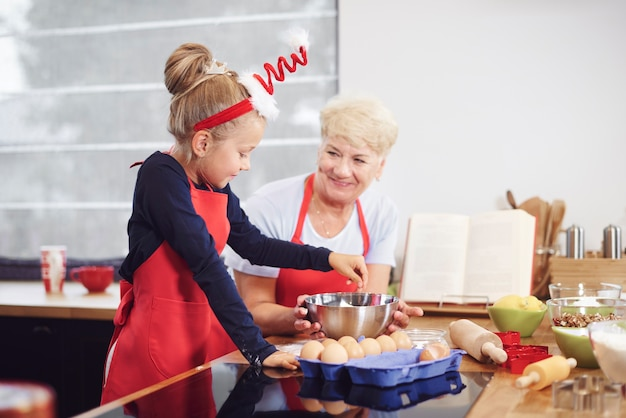 Grootmoeder met meisje bakken in de keuken