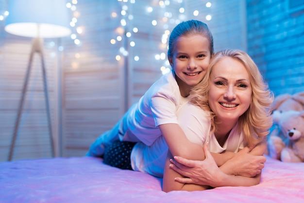 Grootmoeder met meisje omhelst elkaar 's nachts