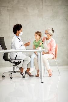 Grootmoeder met schattige kleindochter met vrouwelijke arts op kantoor