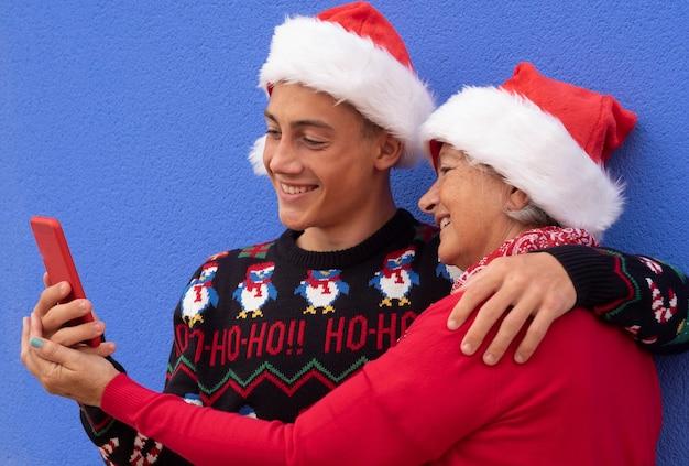 Grootmoeder met tiener kleinzoon glimlachend samen kijkend naar de smartphone, rood gekleed met kersttrui en kerstmuts. concept van vriendschap en liefde