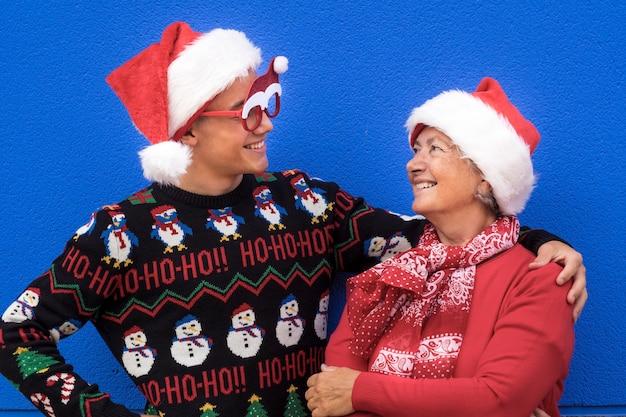 Grootmoeder met tienerkleinzoon die elkaar lacht met rode jurk, kersttrui en kerstmuts. concept van familie, vriendschap en plezier