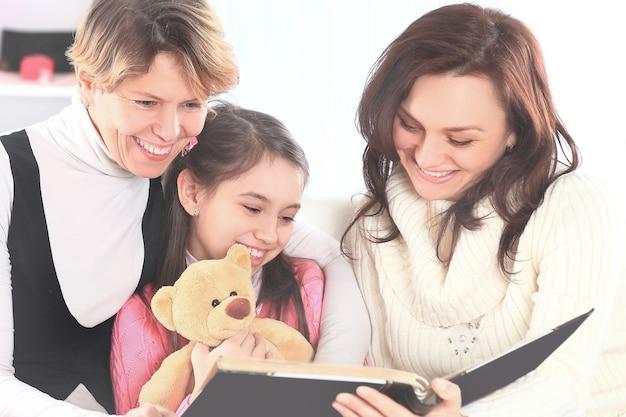 Grootmoeder moeder en dochter lezen samen een boek thuis