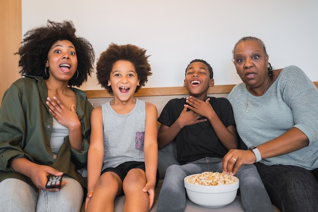 Grootmoeder, moeder en kinderen die thuis naar een film kijken.