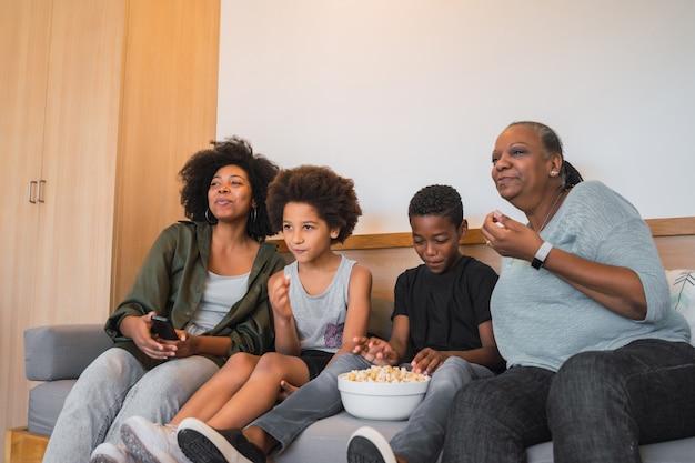 Grootmoeder, moeder en kinderen kijken naar een film thuis.