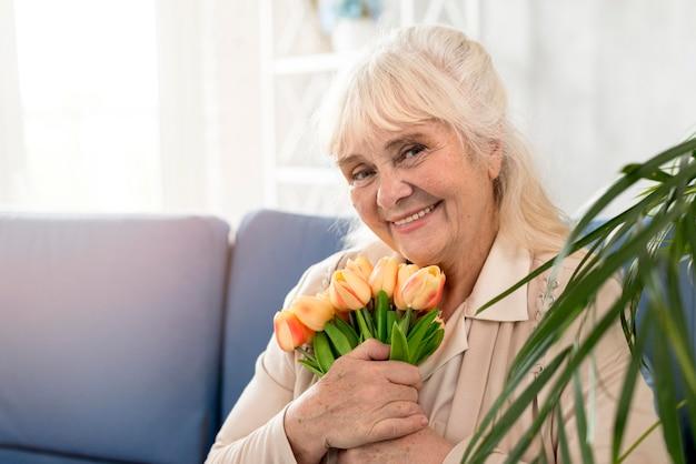 Grootmoeder op bank met bloemen