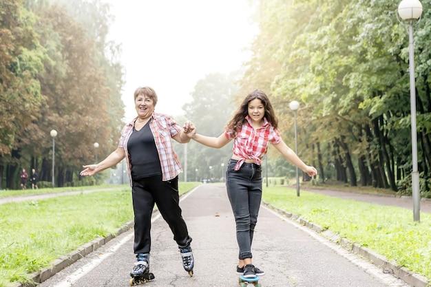 Grootmoeder op rolschaatsen en een kleindochter op een skateboardrit in het park, hand in hand