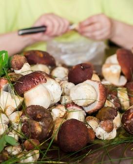 Grootmoeder snijdt porcini-paddenstoelen in een grote gele plaat