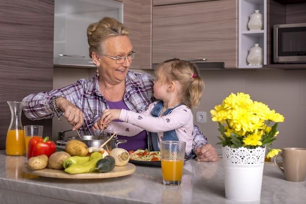Grootmoeder speelt met haar kleindochter in de keuken
