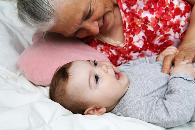 Grootmoeder spelen met haar baby grootvader binnenshuis. senior vrouw met meisje. speeltijd voor meerdere generaties