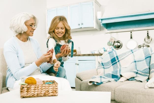 Grootmoeder spelen met haar kleindochter terwijl ze breien.