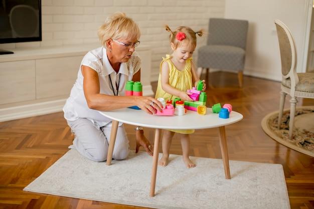 Grootmoeder spelen met kleine kleindochter in de kamer