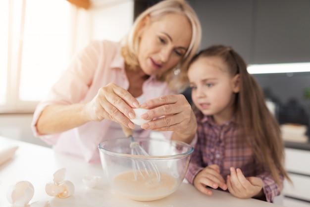 Grootmoeder vertelt het meisje hoe ze een zelfgemaakt koekje moet maken.