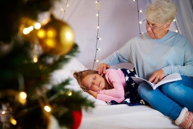 Grootmoeder wiegt kleindochter in slaap