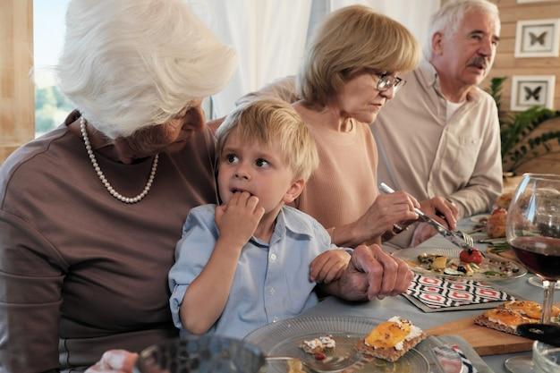 Grootmoeder zit aan tafel met haar kleinzoon en voedt hem thuis