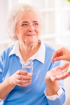 Grootmoeder zit en glimlacht houdt een glas water vast.
