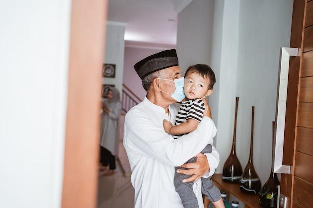 Grootouder die zijn kleinkind thuis kust tijdens een bezoek dat samen met familie eid mubarak viert