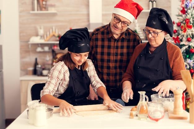 Grootouder op eerste kerstdag kijken naar kind dat dessert maakt