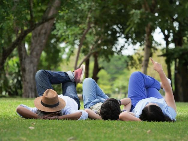 Grootouders brengen de tijd met kleinzoon door, thuis liggen ze op gras in de tuin.
