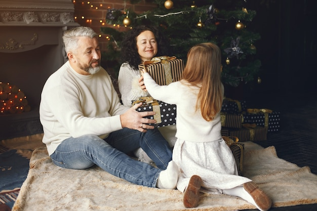 Grootouders die bij hun kleindochter zitten. kerst vieren in een gezellig huis.
