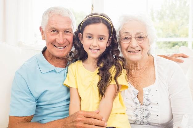 Grootouders die met hun kleindochter thuis glimlachen