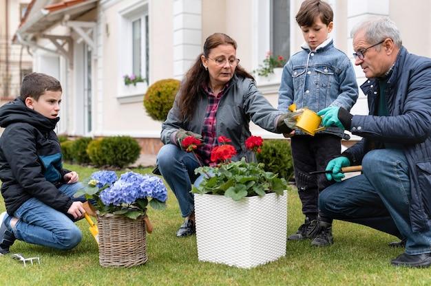 Grootouders die met hun kleinkinderen in de tuin werken