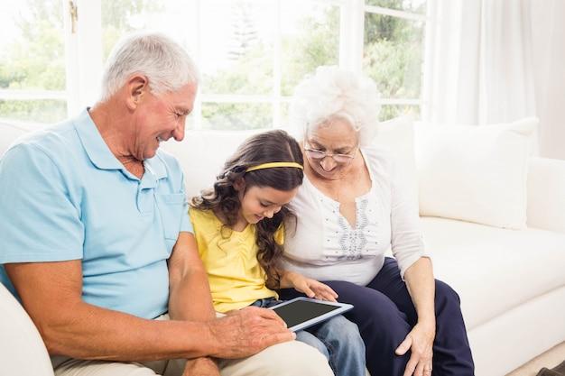 Grootouders die tablet met hun kleindochter thuis gebruiken