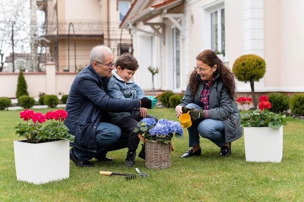 Grootouders en kleine jongen die in de tuin werken