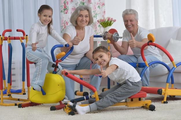 Grootouders en kleine kleindochters doen thuis oefeningen