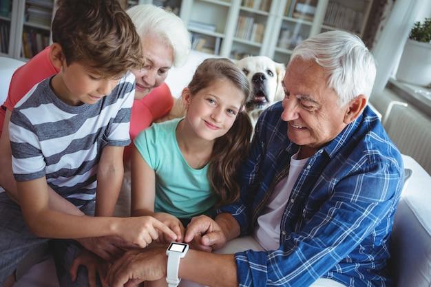Grootouders en kleinkinderen kijken naar smartwatch in de woonkamer