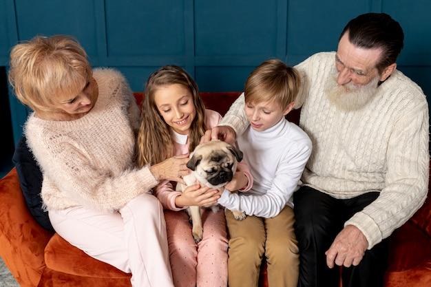 Grootouders en kleinkinderen spelen met hond