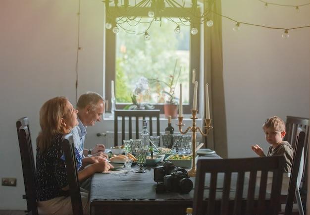 Grootouders en kleinzoon zitten aan tafel tijdens het diner