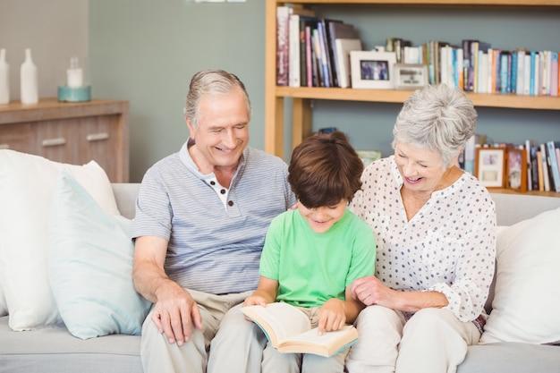 Grootouders helpen kleinzoon tijdens het lezen van boek in de woonkamer
