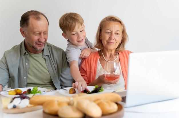 Grootouders laten iets op hun laptop zien aan hun kleinzoon