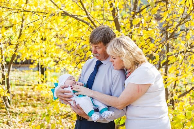 Grootouders met een baby, een kleine jongen die in de herfst in het park of bos loopt. gele bladeren, de schoonheid van de natuur. communicatie tussen een kind en een ouder.
