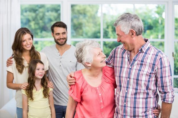 Grootouders omarmen terwijl familie naar hen kijkt