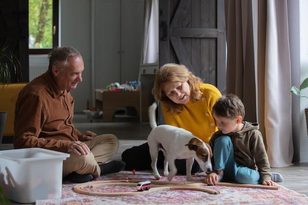 Grootouders spelen thuis de trein met hun kleinzoon.