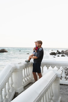 Grootvader die kleinzoon houdt en op zee kijkt