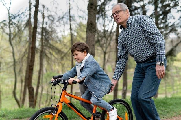 Grootvader die zijn kleinzoon leert fietsen