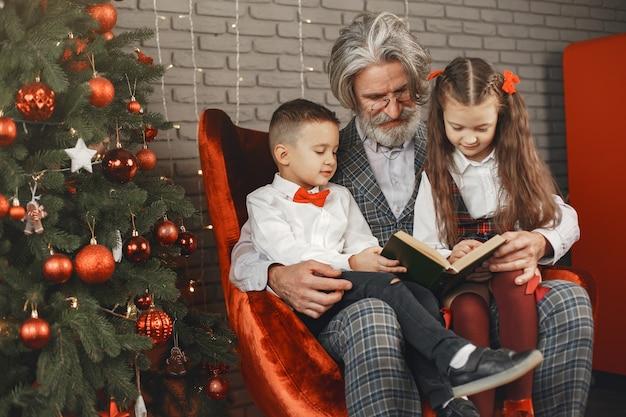 Grootvader draagt een bril, leest een boek voor kleine kleindochters tweeling in een kamer ingericht voor kerstmis. kerst vakantie concept. contrast fotografie