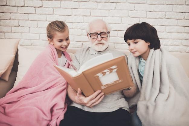 Grootvader en gelukkige kinderen kijken naar fotoalbum.