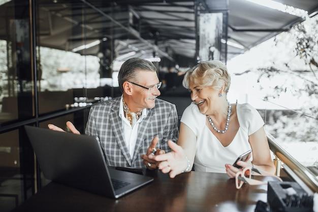 Grootvader en grootmoeder met bril zitten in café van open laptopcomputer en glimlachen