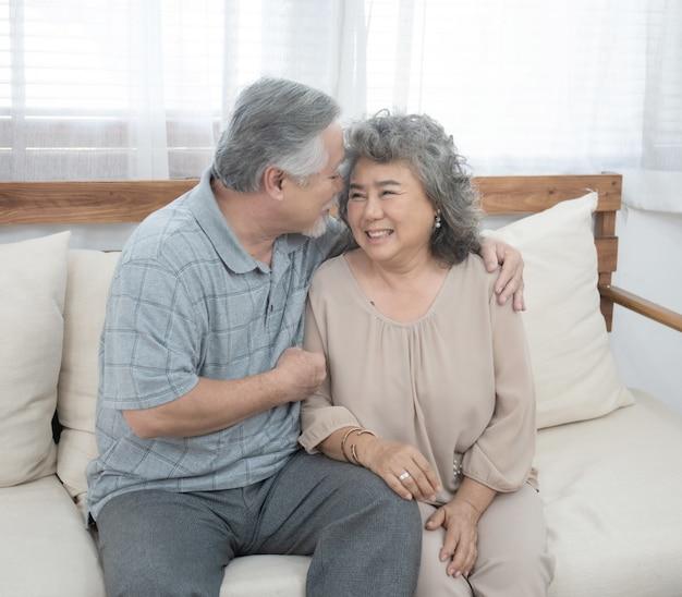 Grootvader en grootmoeder zitten op de coach in de woonkamer thuis hebben vrije tijd in pensioen levensstijl.