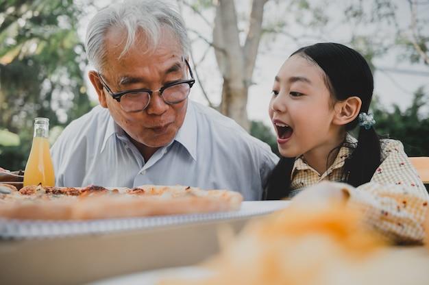 Grootvader en kleindochter hebben pizza in de tuin thuis. pensioenleeftijd levensstijl met familie op zomervakantie.