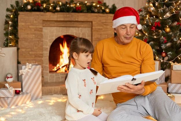 Grootvader en kleindochter leesboek bij open haard en kerstboom, opa en kleinkind