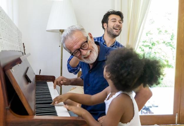 Grootvader en kleindochter spelen piano terwijl vader naast hen zit familieconcept