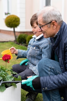 Grootvader en kleine jongen die in de tuin werken